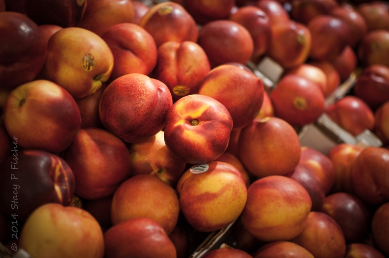 Close-up view of display of red and yellow nectarines.