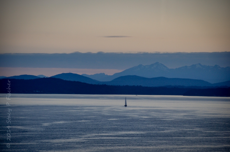 Dusk in Puget Sound creates layers of light and deep blue out of the sky, mountains, water, and lone sailboat.