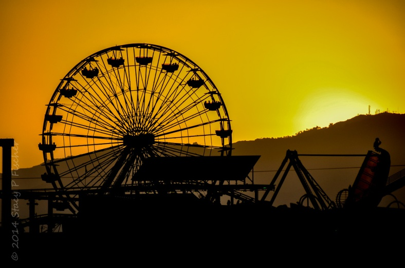 Santa Monica Pier Ferris wheel silhouetted against a sunset of bright orange and yellow.