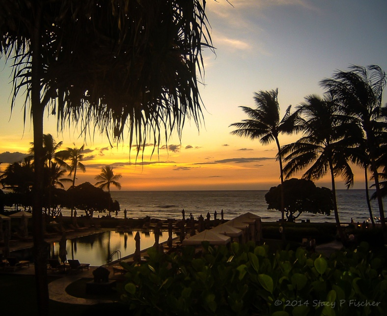 Sunset over beach at Hualalai, Hawaii creates silhouetttes of palm trees, sightseers, swimming pool and cabanas.
