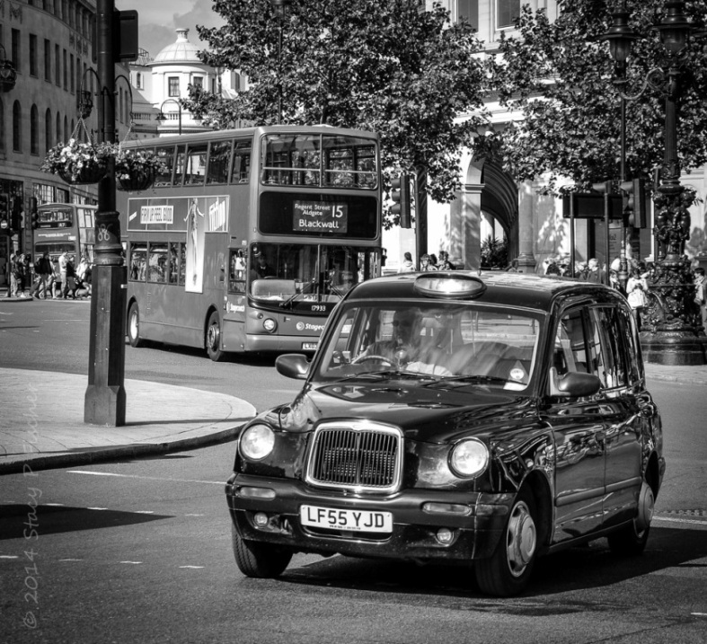 Black and white image of London taxi in foreground, London double-decker bus in background, entering a roundabout.