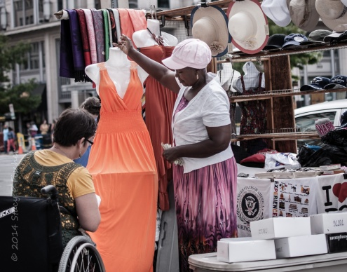 Female street vendor holds up orange dress for wheelchaired customer to view