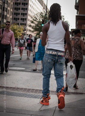 Rear view of man crossing a city street wearing bright orange Tony the Tiger high tops.