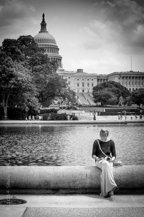Woman sitting on the edge of a pond, reading, with US Capitol in the background.