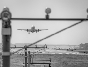 A plane lifting off at the end of the runway, viewed through the support of the runway landing/take-off lights