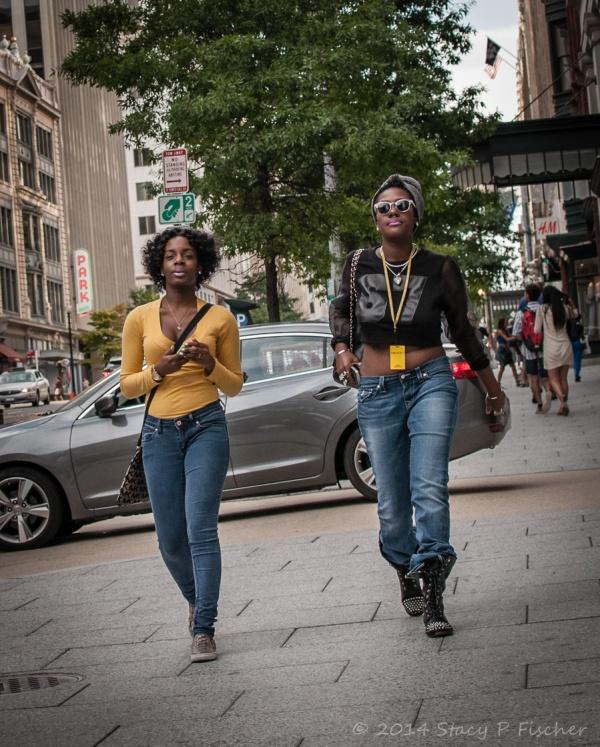 Two woman walking side-by-side on sidewalk, both wearing yellow