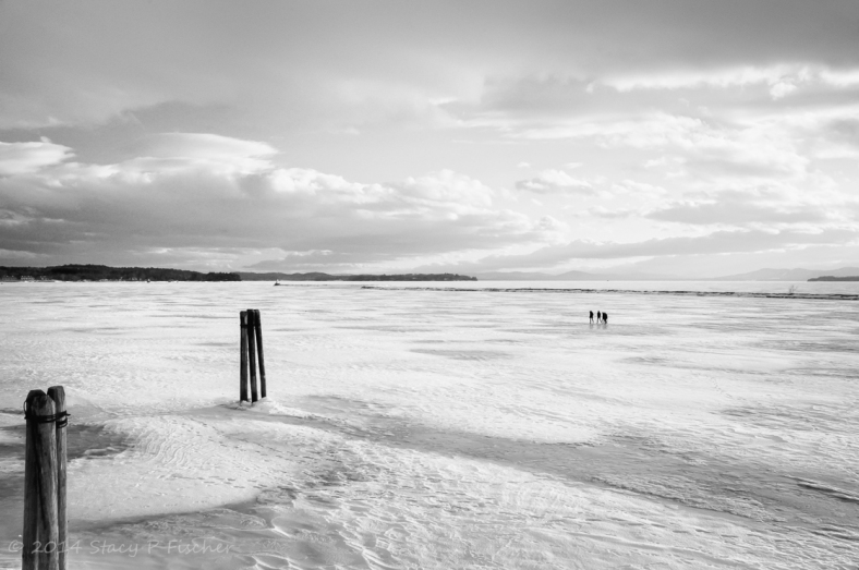 Lake Champlain, frozen over, with a group of three people in the distance walking on it.