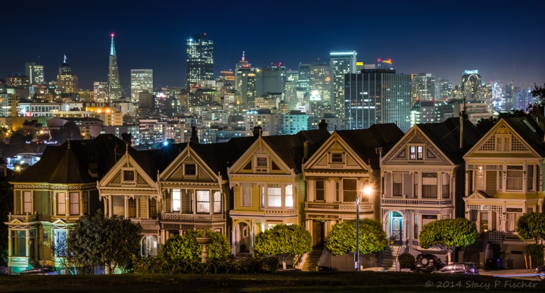 Painted Ladies of San Francisco at night glow against the backdrop of the sparkling San Francisco skyline.