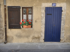 Blue door and red geraniums in window of home in Bonnieux, France