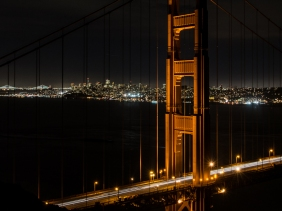 Golden Gate north tower at night, with city lights of San Francisco and Bay Bridge in the distance