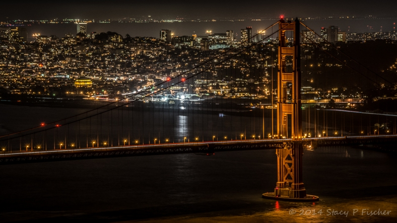 Golden Gate south tower at night, with city lights of San Francisco in the background