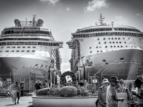 Two cruise ships docked side-by-side shows their massive scale.