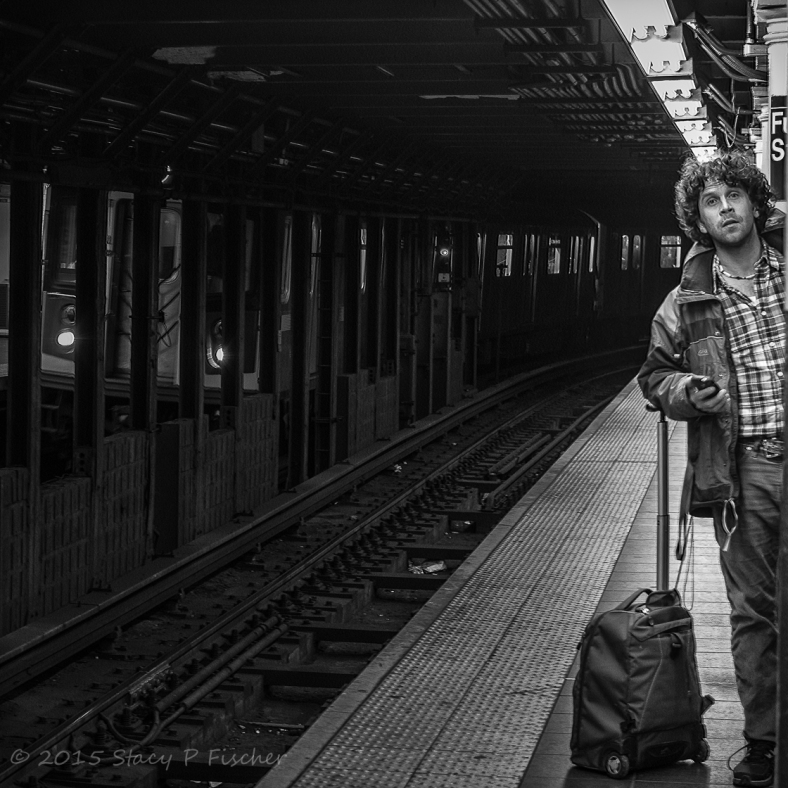 Man peering down New York City subway tracks, waiting for next train.