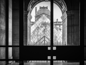 Louvre Pyramid viewed through a shadowed archway.