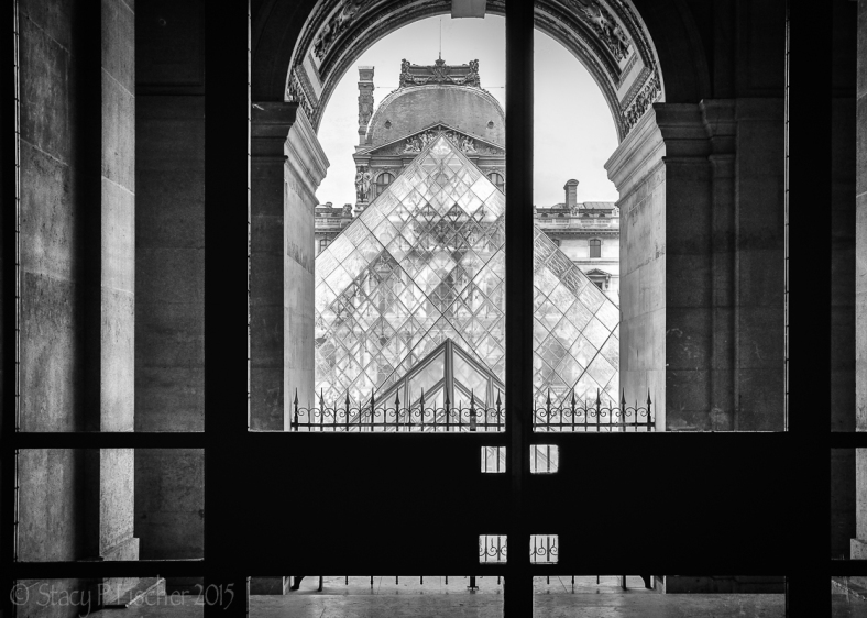 Louvre Pyramid viewed through an alcoved archway.