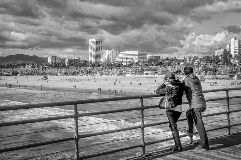 Couple views Santa Monica Beach from the pier.