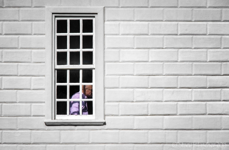 White windows panes with man in purple shirt.