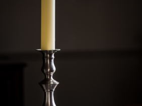 Pewter candlestick illuminated by sidelight.