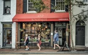 Three pedestrians walk past Cafe Bonaparte, Georgetown, Washington, DC