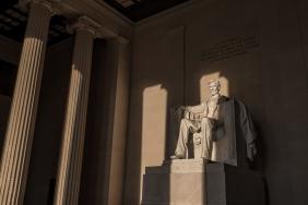 Sunrise illuminates the statue of Lincoln within the Lincoln Memorial