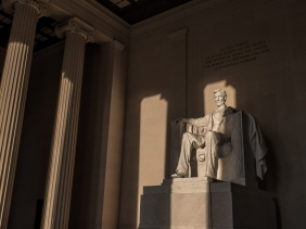 Sunrise illuminates the statue of Lincoln within the Lincoln Memorial