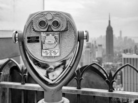 Binocular viewer atop Top of the Rock with Empire State Building in the background.