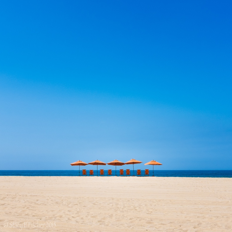 Orange umbrellas and chairs on a beach silhouetted against the bright blue of the sky and water.