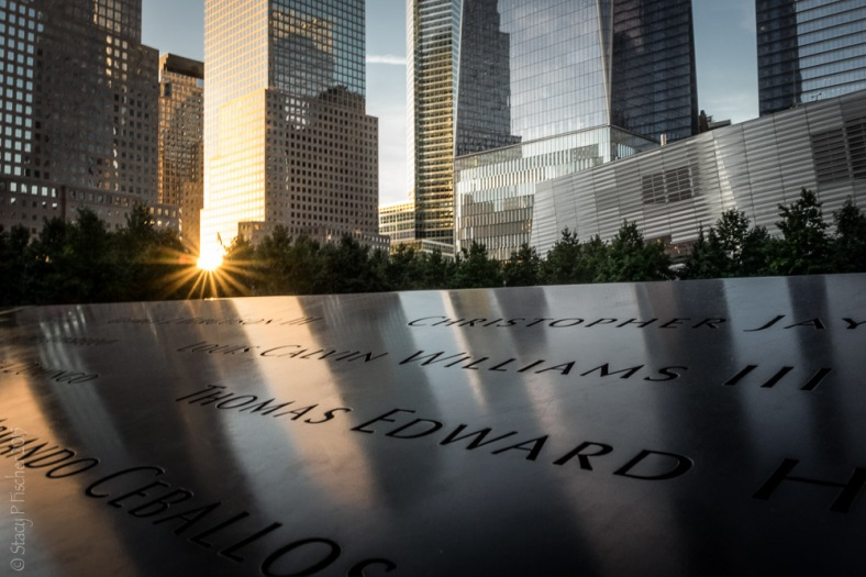 Setting sun cast reflections onto name-inscribed bronze plate of the 9/11 Memorial South Tower reflecting pool.