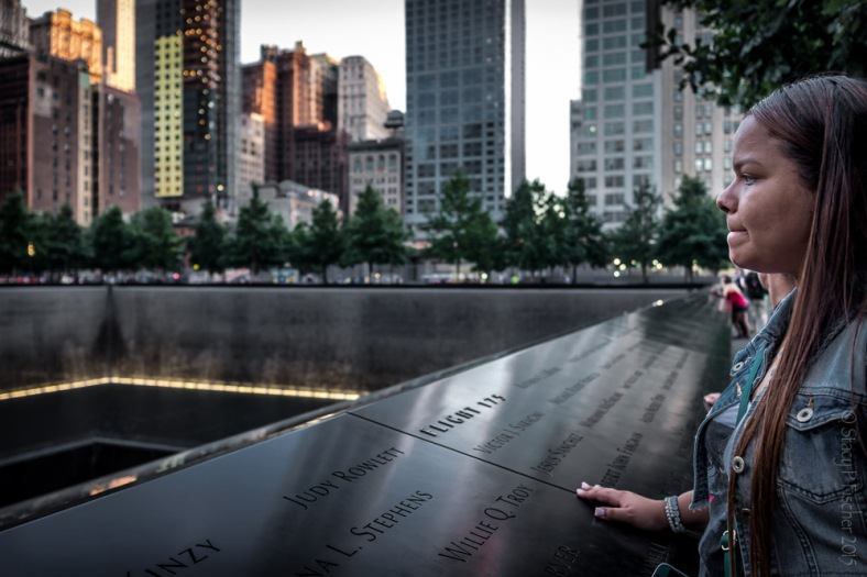A woman stares out over the 9/11 Memorial South Tower reflecting pool.