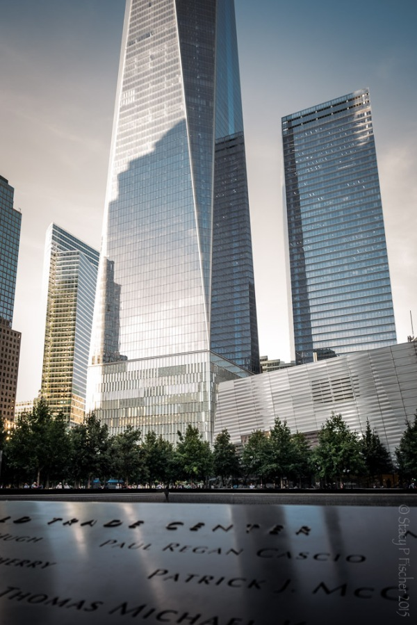 Looking across inscribed names on bronze plate of South Tower reflecting pool to One World Trade Center.
