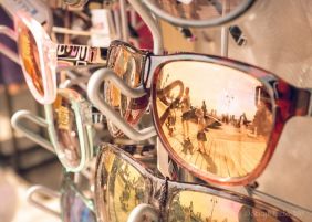 Sunglasses in stand reflecting summer activity on boardwalk