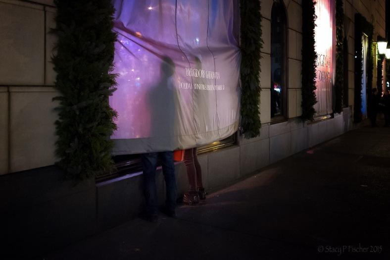 Two people peek underneath Bergdorf Goodman window curtain to see 2015 Christmas display