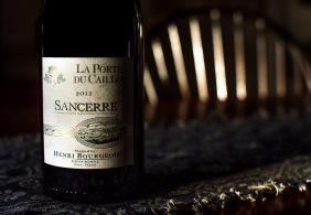Bottle of Sancerre wine on a table in the shadows of afternoon sun