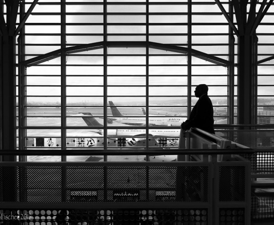 Man silhouetted against windows of Washington National Airport