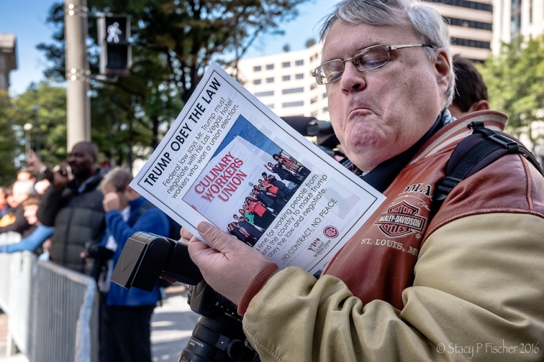 Man reads union flyer about Trump International Hotel DC protest